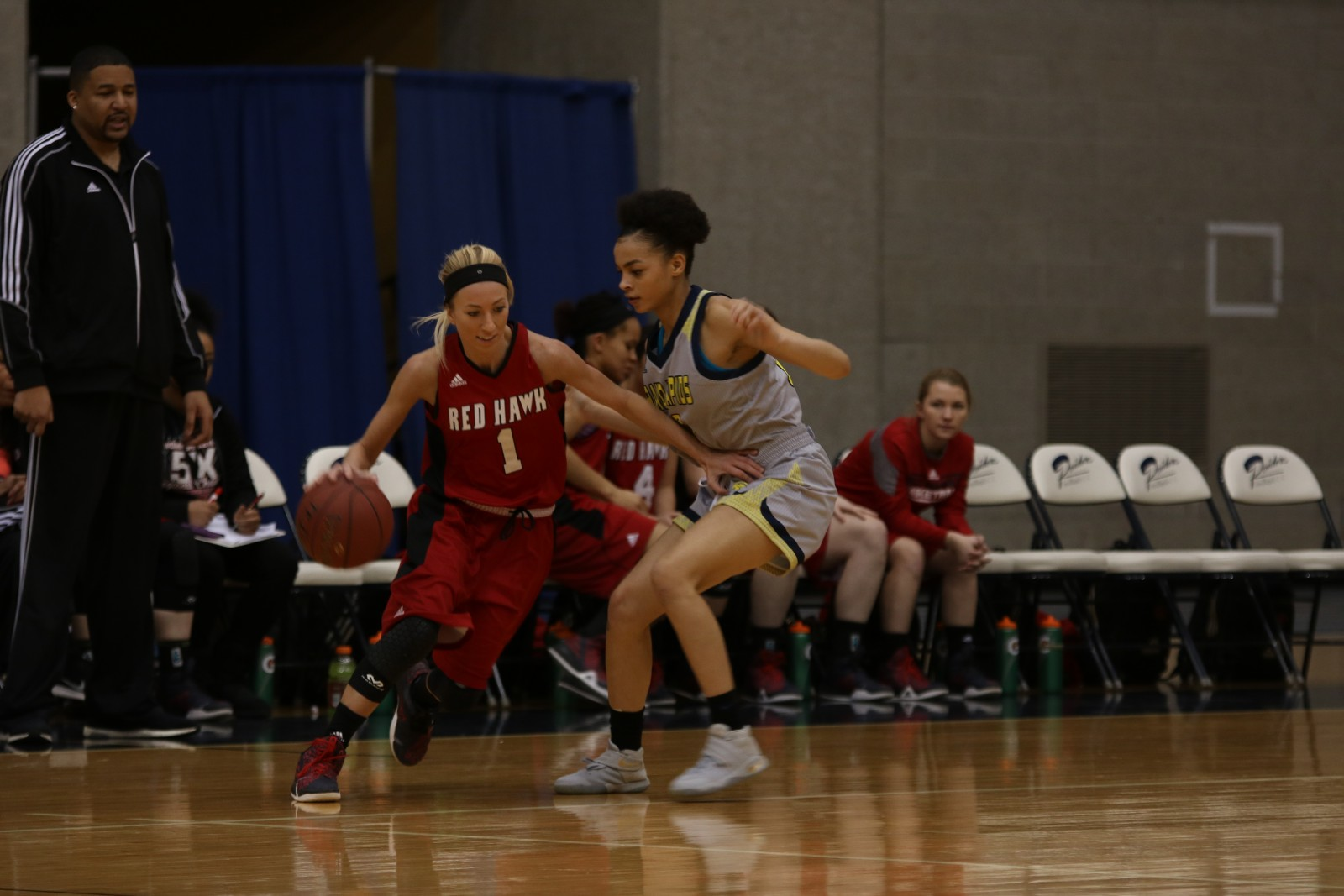 Freshman Guard, #23, Allazae Lloyd guarding Lake Michigan Sophomore Guard, #1, Kelsey Kinder.