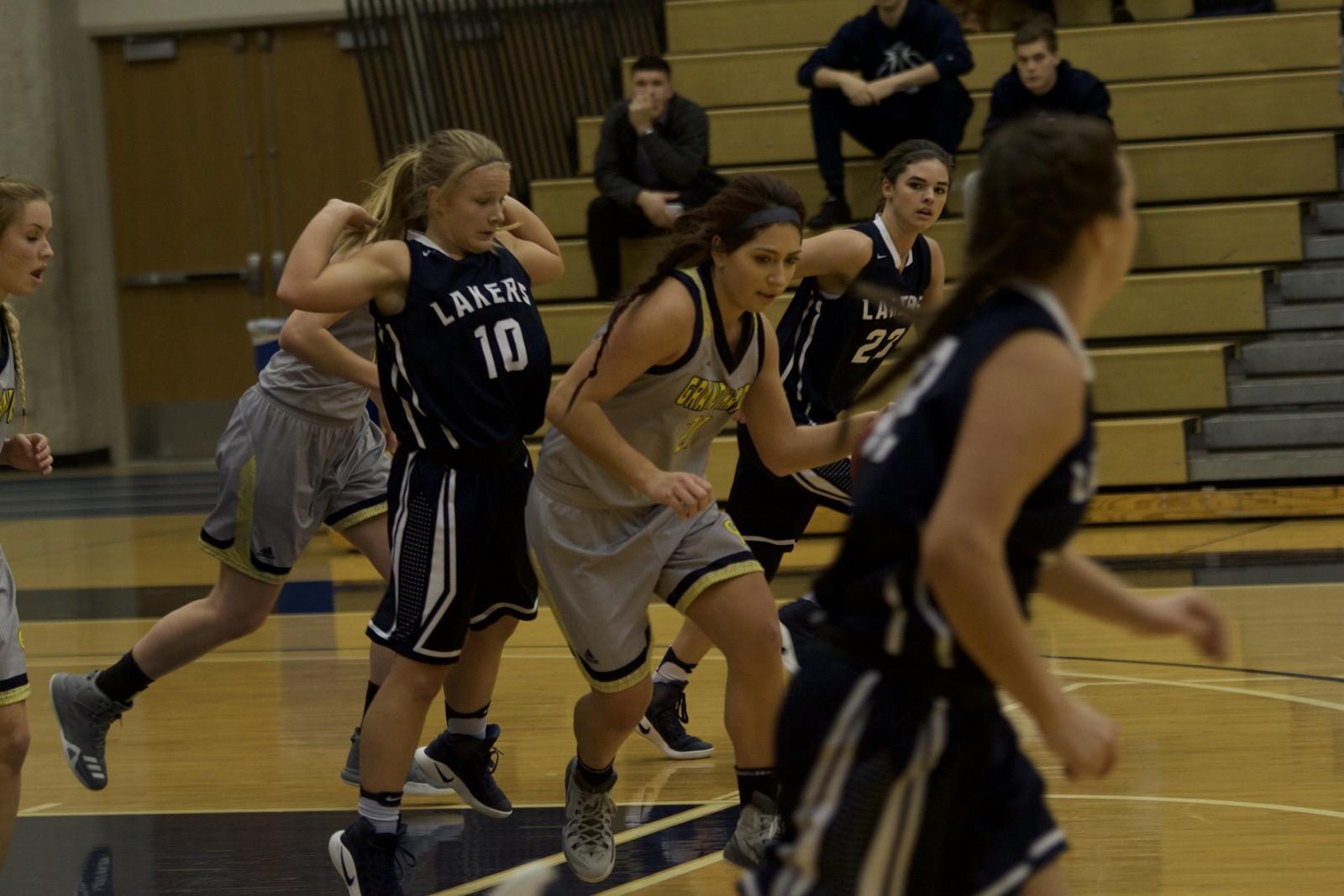 Freshman Guard, #21, Maddie Albert driving through traffic as the Raiders push the ball down the court.
