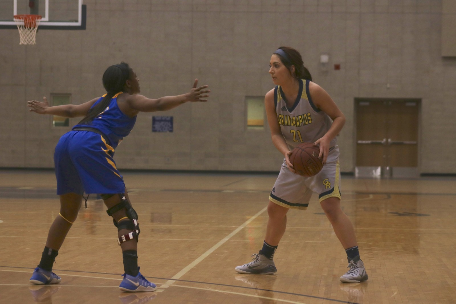 Freshman Guard, #21, Maddie Albert on the perimeter as she looks for the open player for GRCC.
