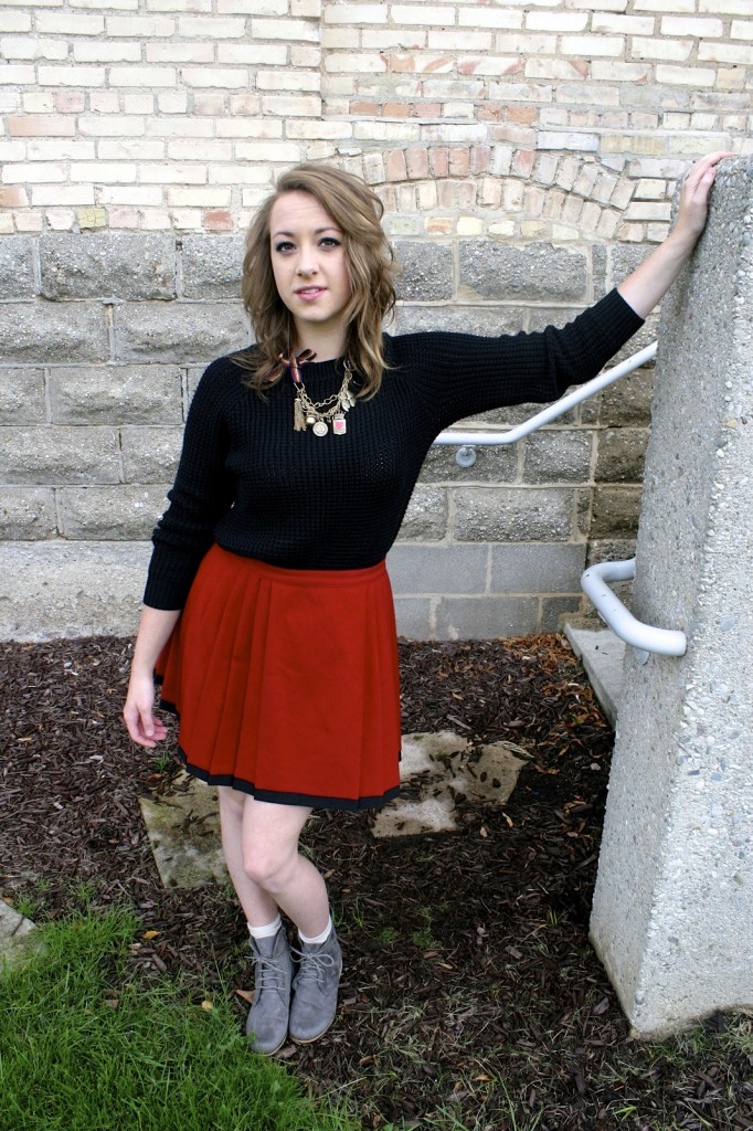 The model sports a black-chunky sweater from Forever21 ($13) paired with a vintage red cotton skirt ($15) from College Town Vintage. Throw tights ($7.50), combat boots ($40), and spiky jewelry to give the outfit some edge if you're feeling spunky! This look is perfect for a typical school day that is both warm and adorable.