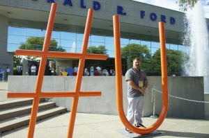 """Artist Mark Vainner stands next to his entry """"Search and Find You"""" at the Gerald R. Ford Presidential Museum. Photo by Jacquelyn Zeman"""