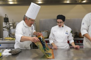 Chef Gilles Renusson shows Alexis Rice how to mix coloring into the molten sugar. Photo by Jonathan D. Lopez