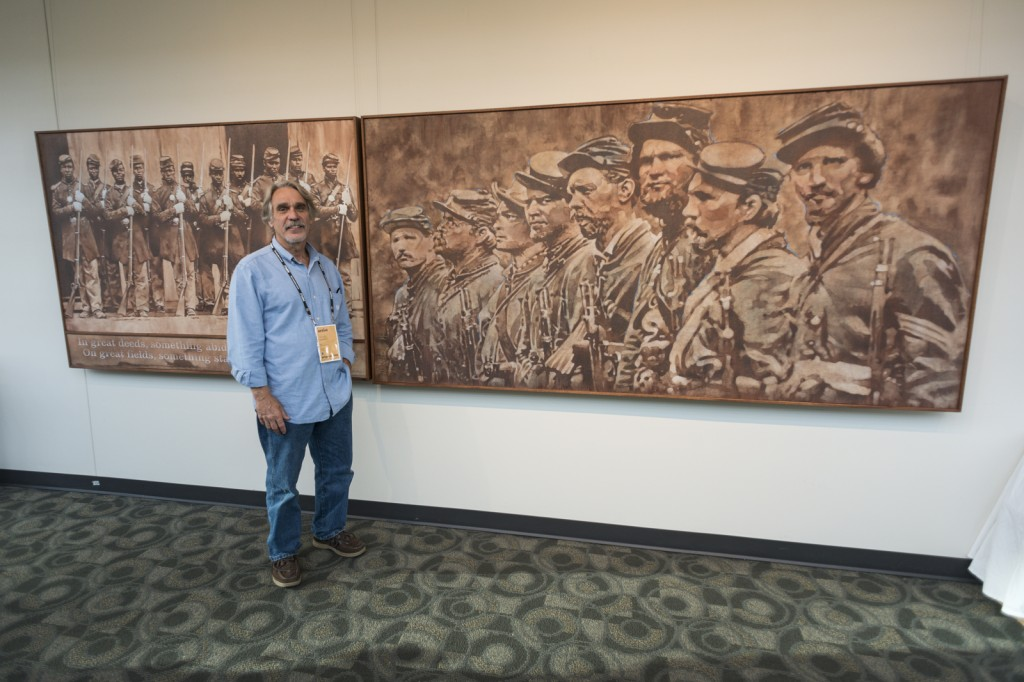 """Artist Andrew J. Woodstock stands next to his entry """"Brothers in Arms"""" at the DeVos Place Convention Center."""