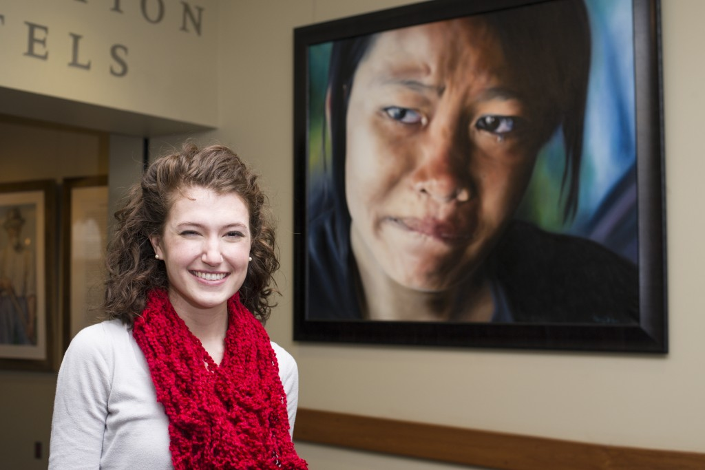 """Gretchyn Lauer, winner of the 2D category of ArtPrize, stands in front of her painting, """"Outcry"""".  Photo by Jonathan D. Lopez"""