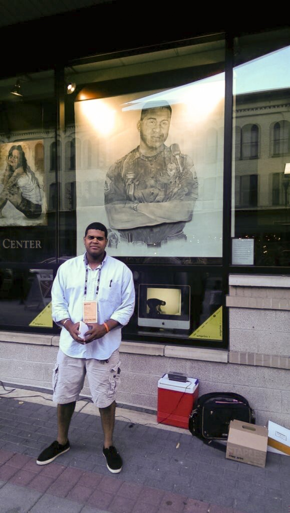 Arturo Araujo standing in front of his pencil drawing entitled 'End of Watch' located at the Grand Rapids Police Department.