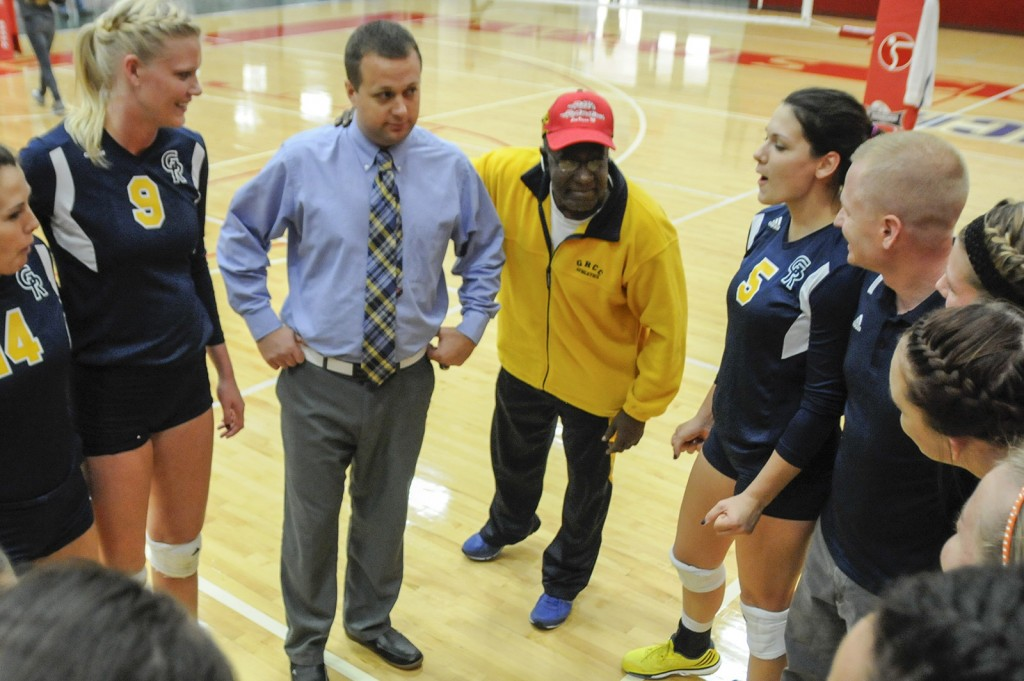 Charlie Wells (center) addresses the women's volleyball team after winning the regional finals in 2014.
