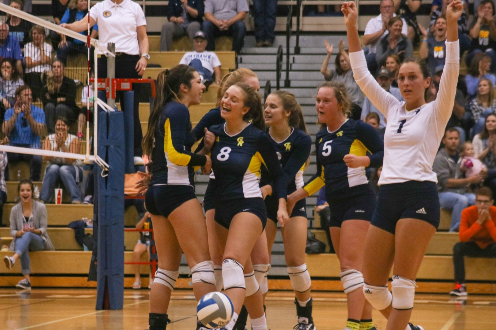 The GRCC volleyball team gets fired up as they score a point against Muskegon CC during the fifth and final set of the night.