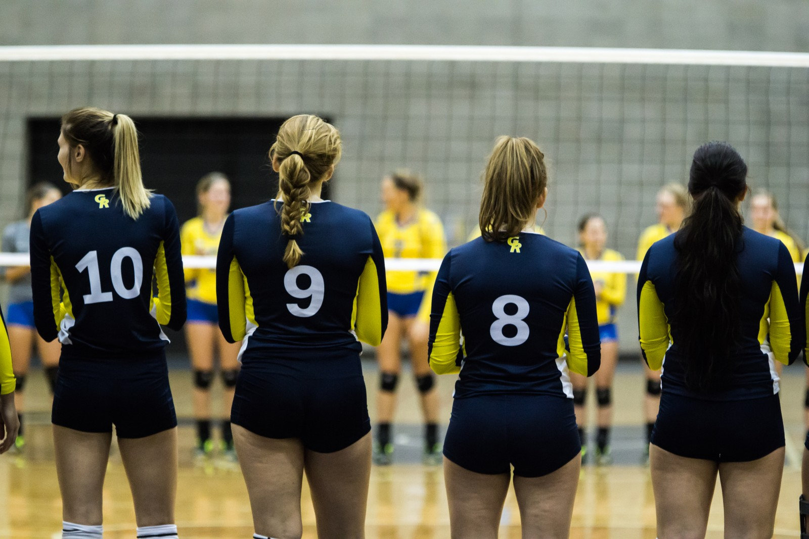 Kylie Frank from the Muskegon game, earlier this year, with teammates on her right and left, waiting to start the game.