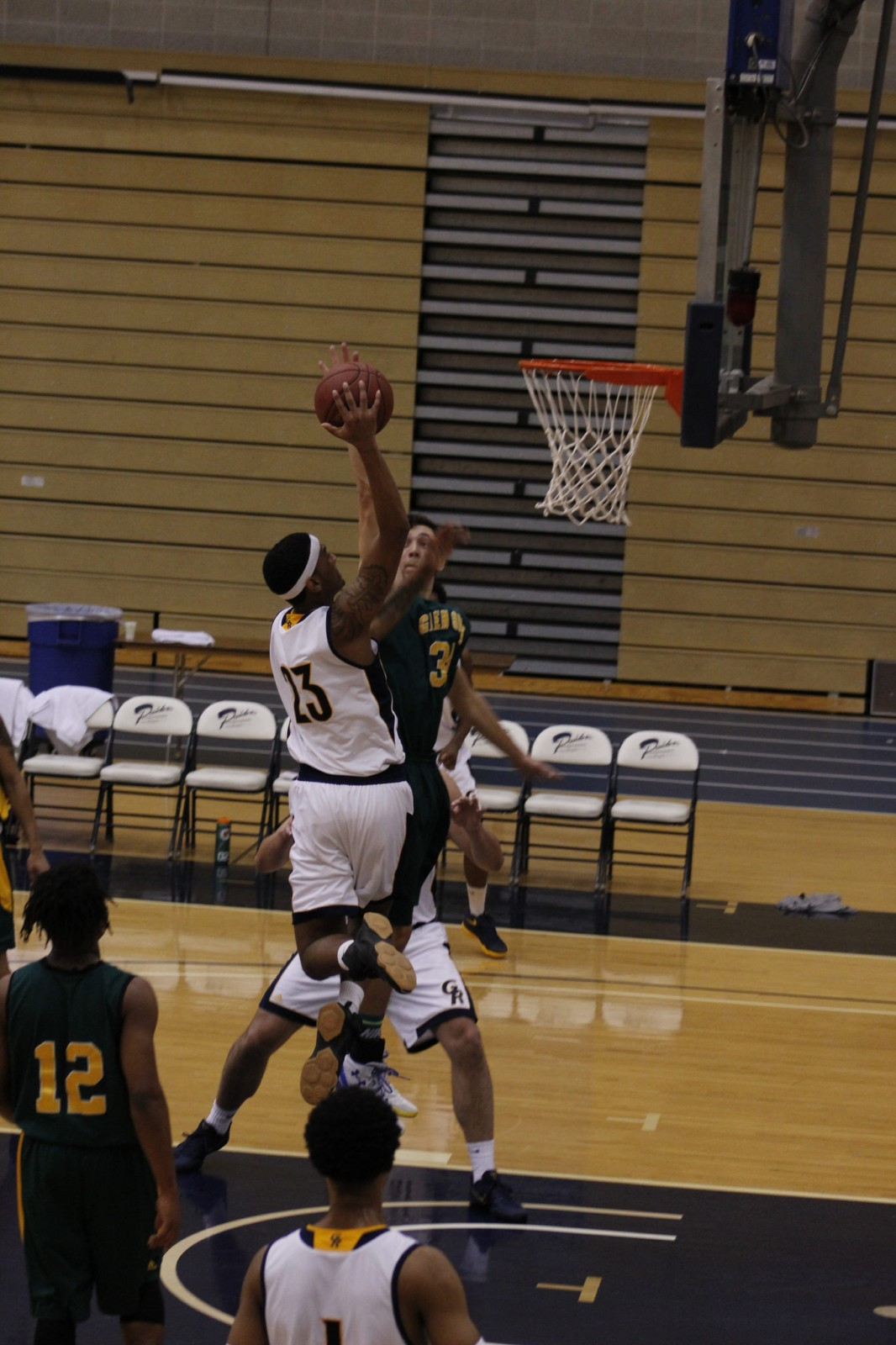 Freshman Forward, #23, Corey jones goes in for the contested layup against Glen Oaks CC.