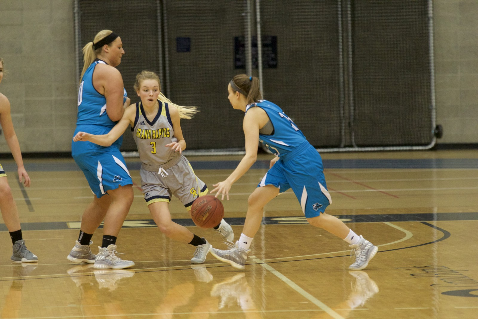 Freshman guard, #3, Claire Flewelling guarding against a KVCC player as she's getting screened.
