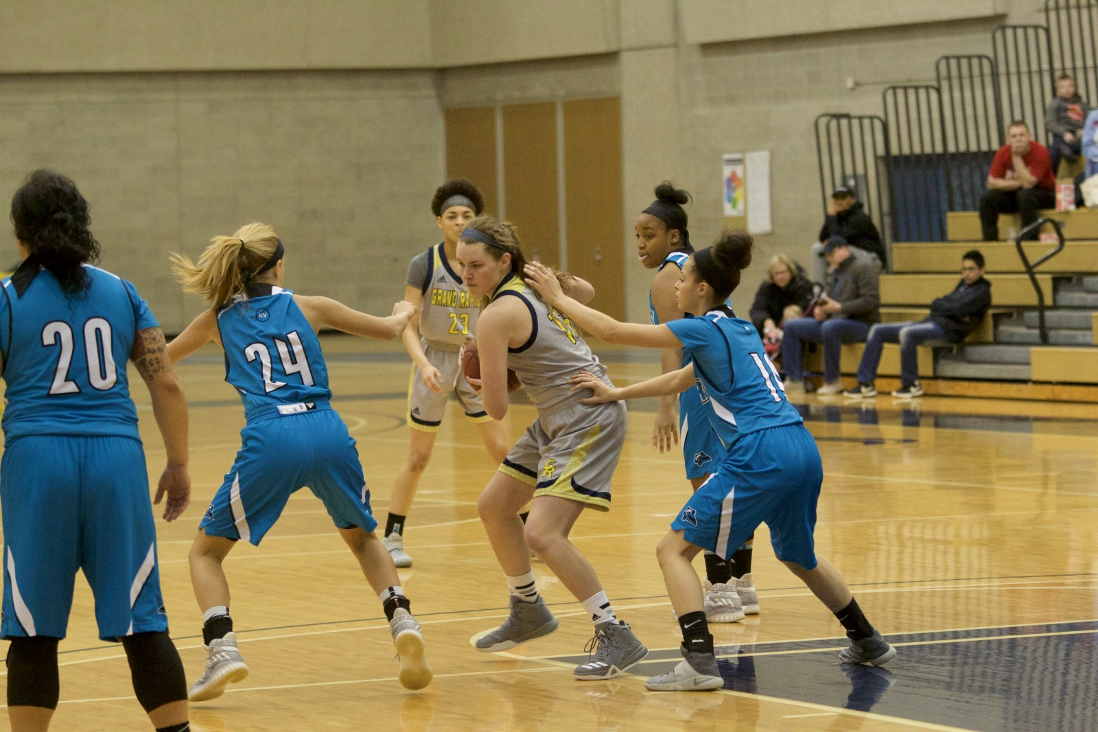 Freshman Guard, #13, Josie Manion towards the top of the key looking to pass the ball as two KVCC defenders try to knock the ball away.